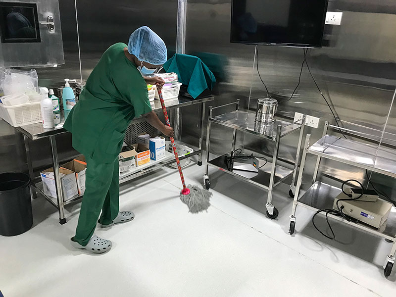 A member of staff wearing green surgical scrubs, a hair net and a mask, mops the operating floor