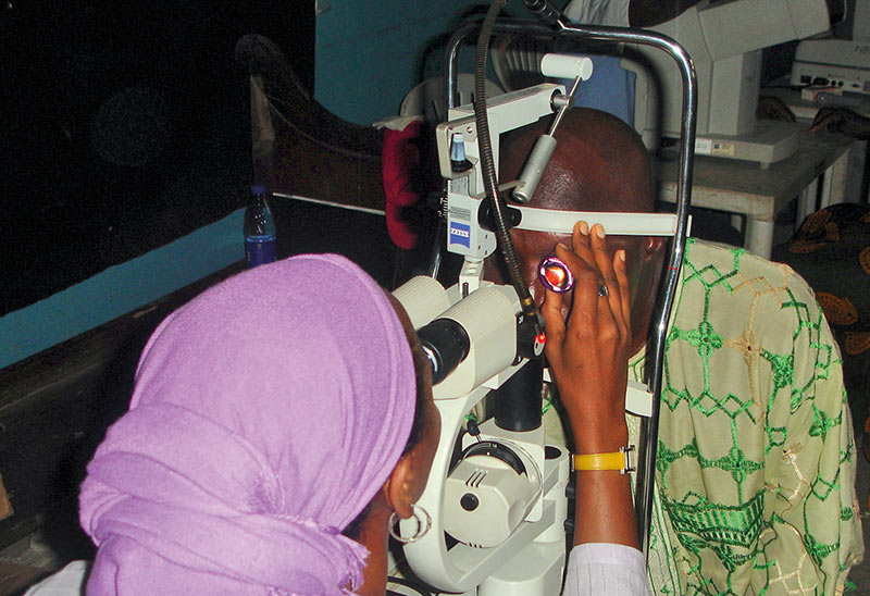 a female ophthalmologist examines the eye of a male patient at the slit lamp