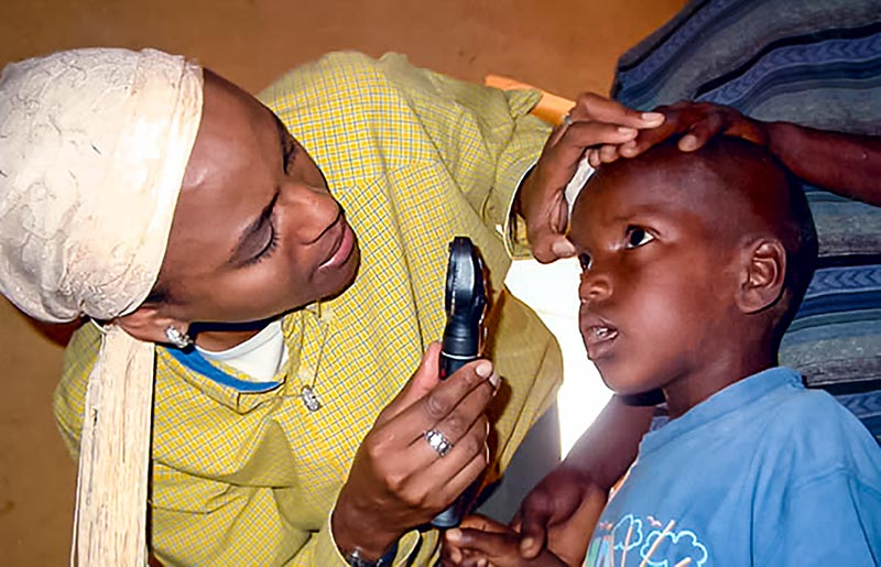 Ophthalmologist examine a child's eye with a handheld ophthalmoscope