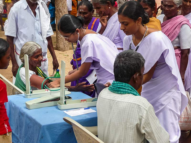 Female Indian ophthalmic nurses checking the blood pressure of patients using sphygmomanometers