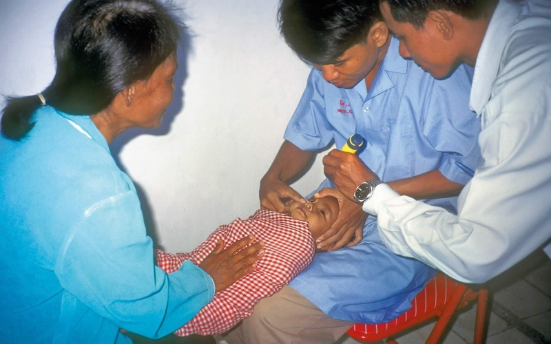 Primary health care workers examine a baby. CAMBODIA. © Sue Stevens