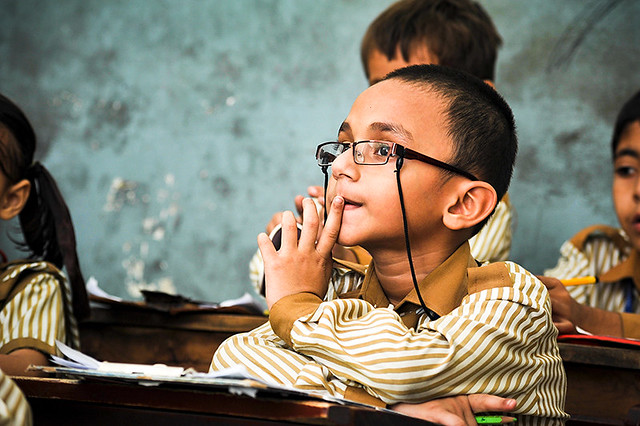 School boy sitting at a desk wearing spectacles
