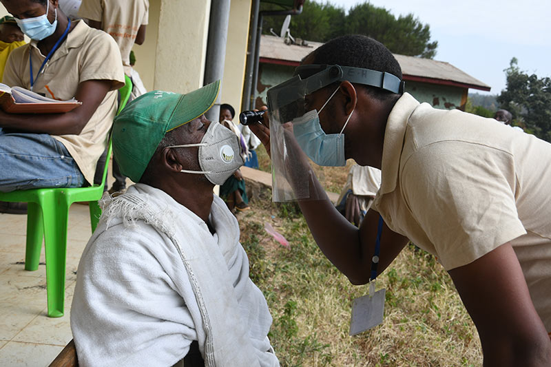 A male eye care team member wearing a face visor and mask uses a torch to look at the eye of a male patient who is wearing a face mask