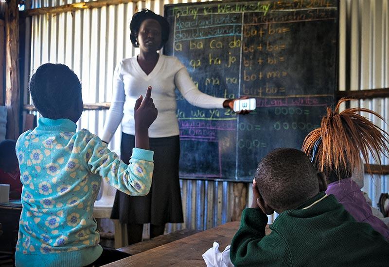 Enseignante tenant devant elle un smartphone montrant l'application PEEK qui permet de mesurer l'acuité visuelle ; elle se tient devant la classe et teste l'acuité visuelle d'un enfant qui montre avec son doigt le sens d'orientation du « E » apparaissant sur l'écran.