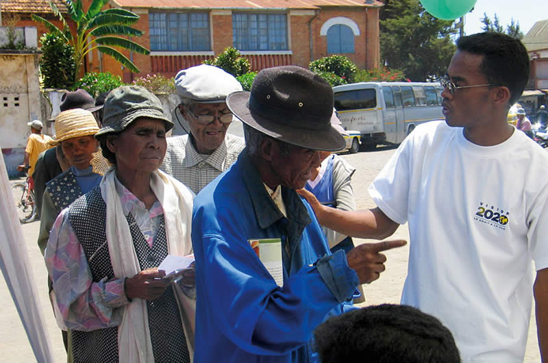 A community eye health worker answering questions from elderly patients about cataract surgery. MADAGASCAR. © Henry Nkumbe