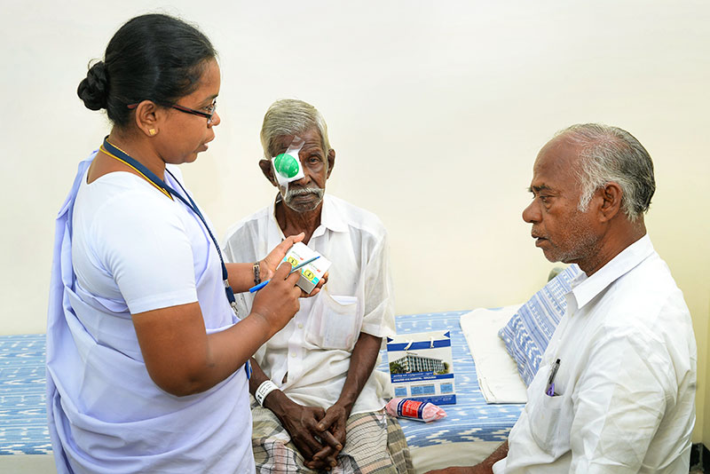 Nurse is talking to member of patient's family whilst patient sits on bed.