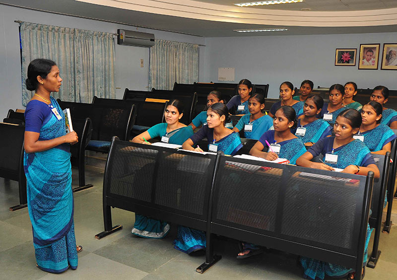 Female tutor standing in front of students in a small lecture room