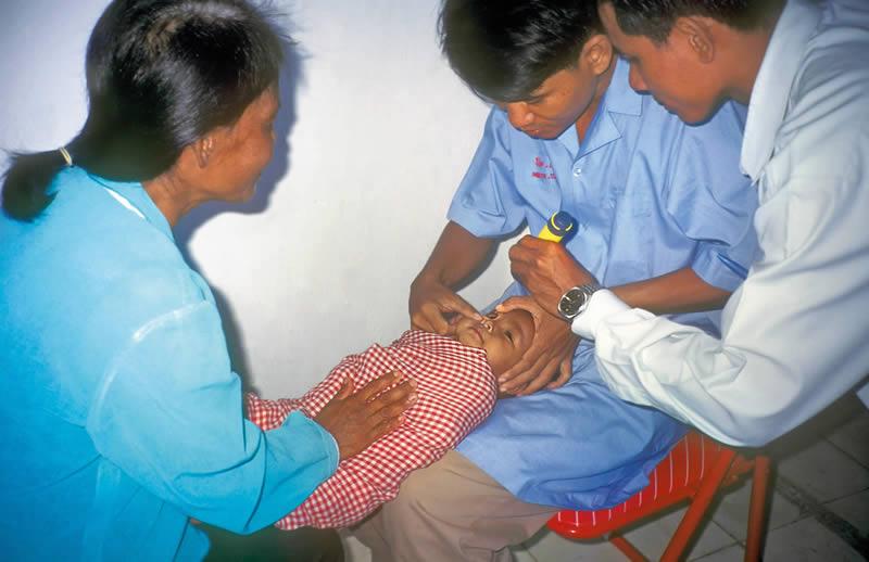 Agents de santé primaire examinant un nourrisson. CAMBODGE. Sue Stevens