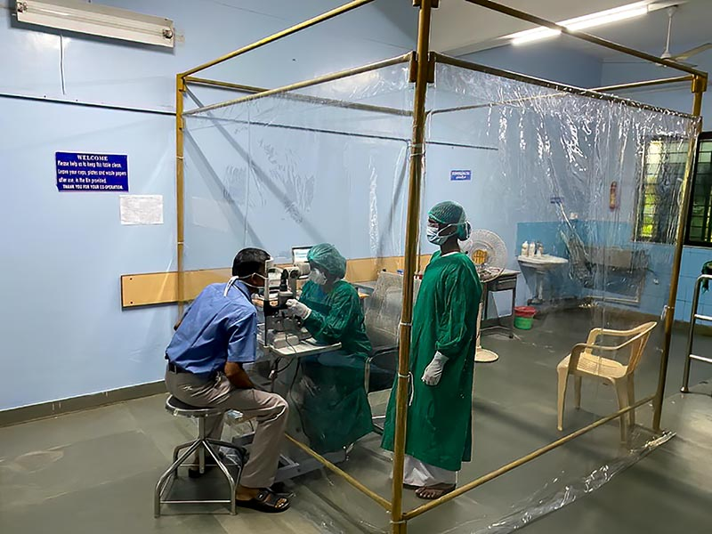Ophtlamologist and eye nurse standing in a clear plastic screened off area (cube) examining a patient's eye. The patient is outside the protective clear plastic sheeting