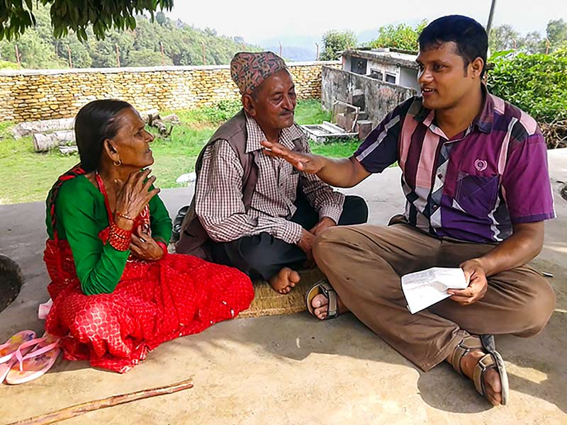 A male counsellor sitting in a village sitting down and talking with a couple