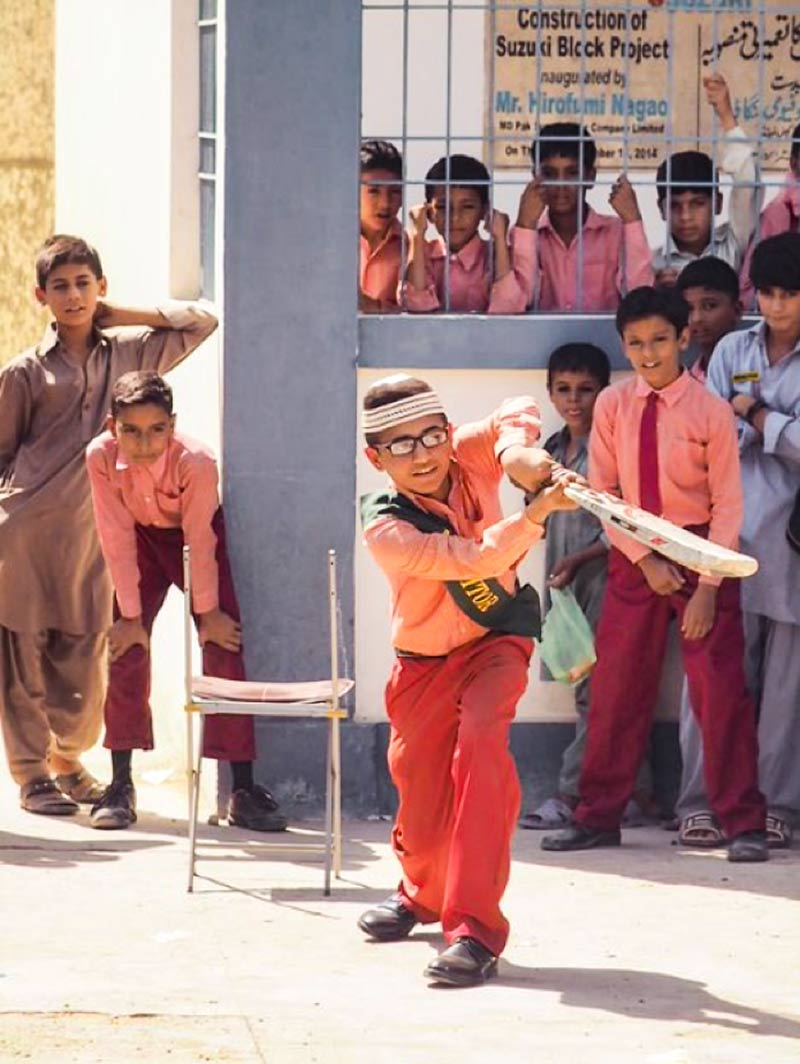School boy batting during a cricket game at school, watched by other pupils
