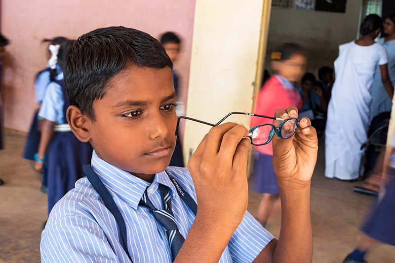 Écolier observant une paire de lunettes qu'il tient dans ses mains.