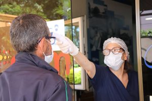 A female nurse wearing scrubs and a face mask holding a thermometer up to the forehead of a patient at the door to the hospital