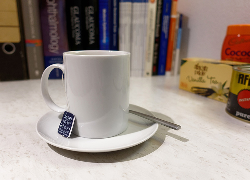 A cup of tea with saucer, tea bag and teaspoon placed on a desk
