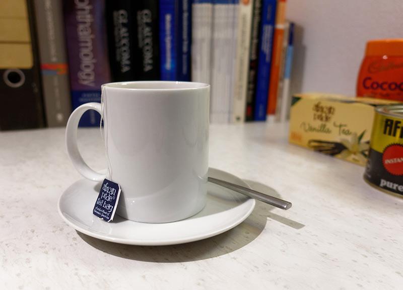 A cup of tea with saucer, tea bag and teaspoon placed on a desk