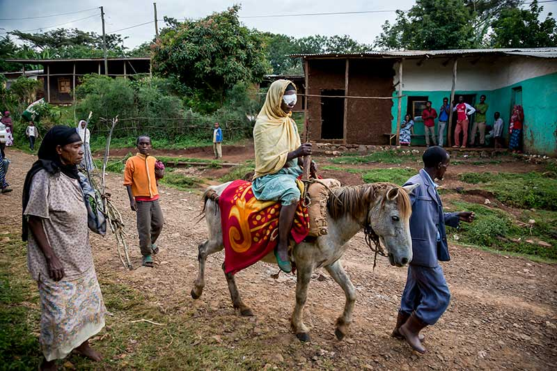 A gentleman leads a donkey though a village carrying a lady wearing eye patches