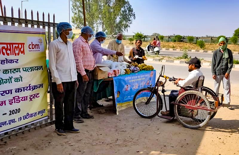 Five people standing at a desk outdoors handing items to a man in a disability vehicle