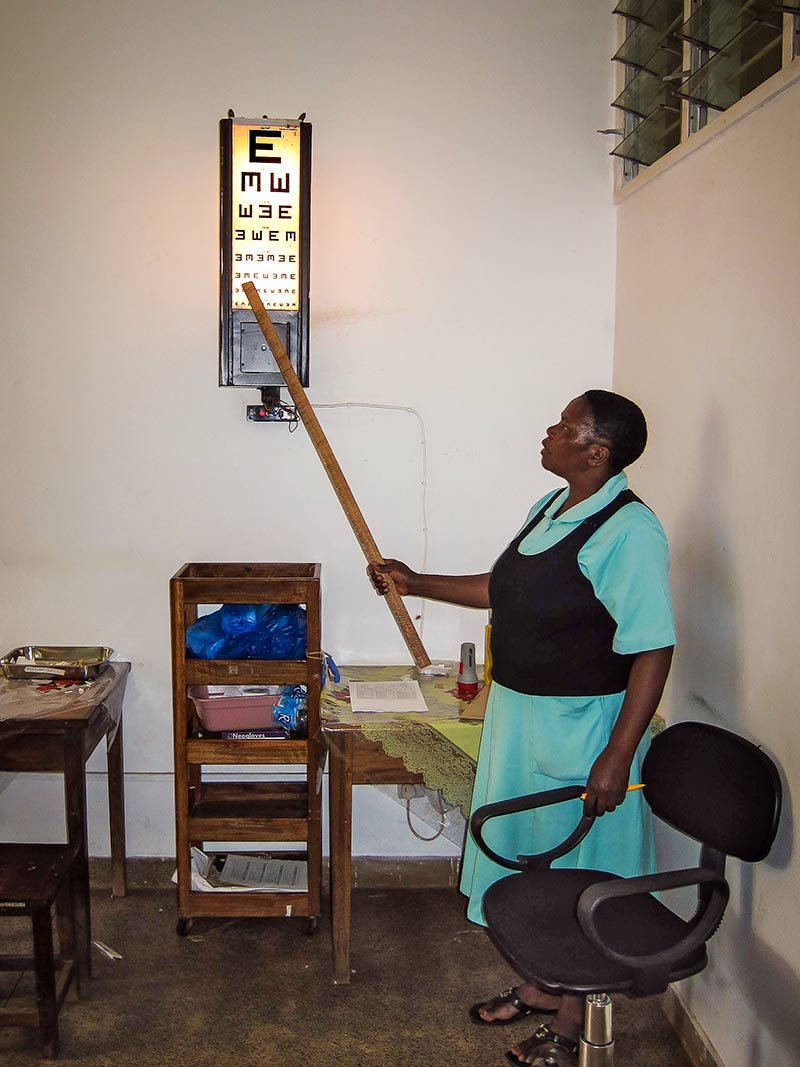 Female ophthalmic staff member pointing to an illuminated tumbling E chart with a wooden pole