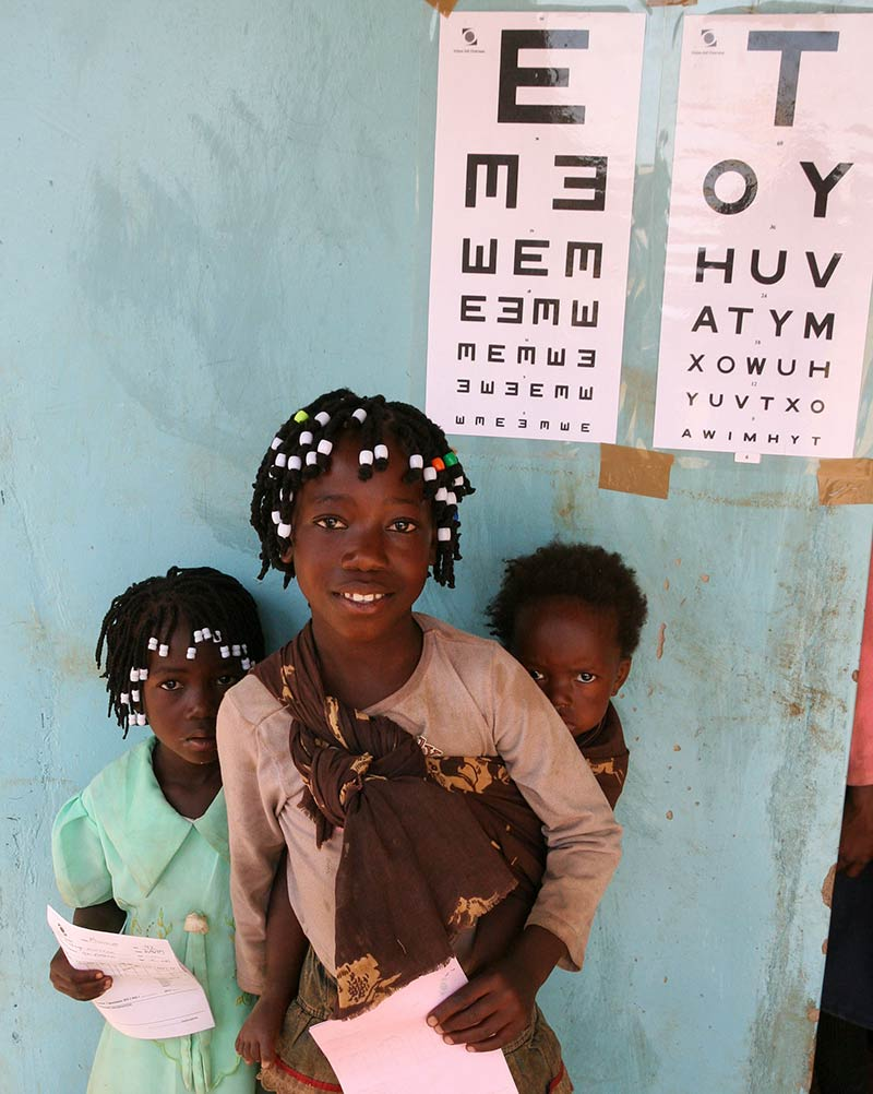 Young girls standing underneath a Tumbling E and a Snellen chart on a wall