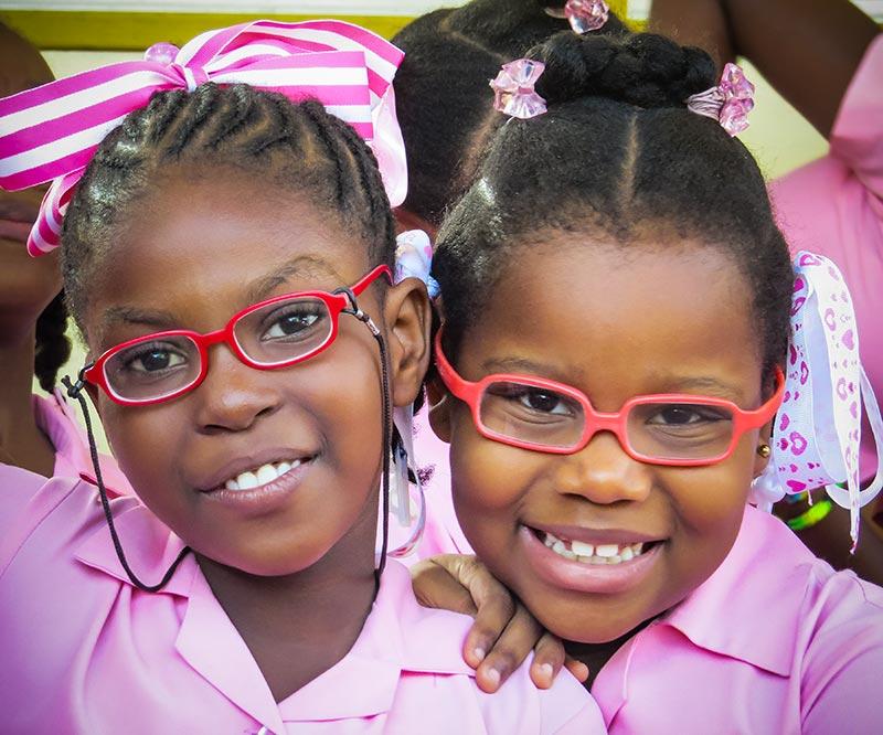 Deux écolières souriantes ; toutes deux portent des lunettes.