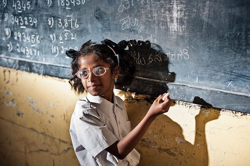 Une écolière portant des lunettes écrit sur un tableau noir avec de la craie, dans une salle de classe.