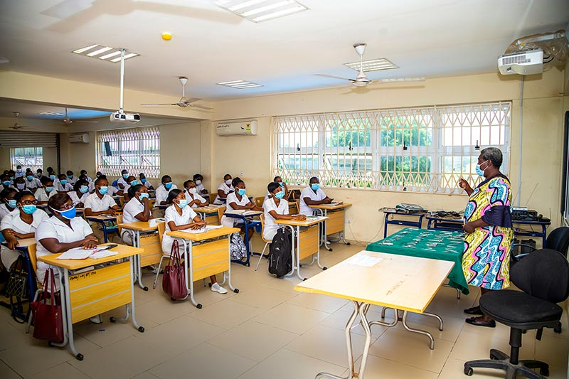 Student nurses sitting in a classroom being taught by a qiulaified/senior nurse who is standing up in front of them