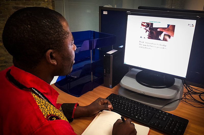 An African male student sitting at his desk, looking at the FutureLearn course on his computer monitor