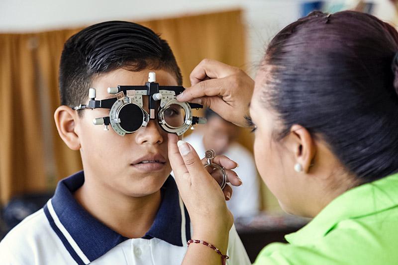 Garçon portant une monture d'essai pendant qu'une optométriste réalise les ajustements nécessaires.
