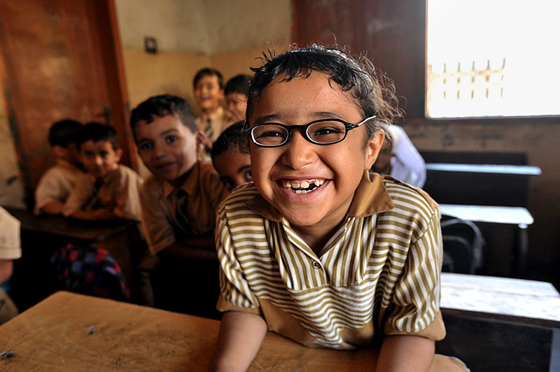School child wearing glasses and smiling in the classroom