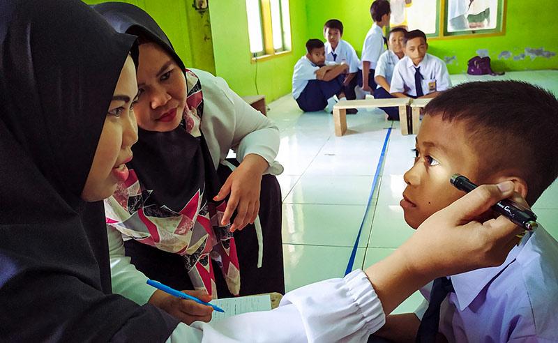 Dans une salle de classe, une agente de santé éclaire latéralement l'œil d'un écolier avec une lampe de poche. Une autre agente de santé est accroupie à côté d'elle et regarde l'écolier. Au fond de la classe, cinq écoliers en uniforme sont assis par terre.