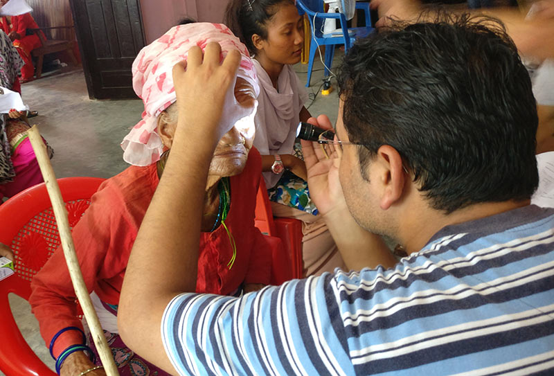 Male eye care staff member examines a lady's eyes using a torch