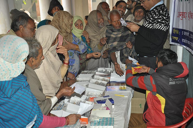 Elderly villagers crowding around a table of spectacles