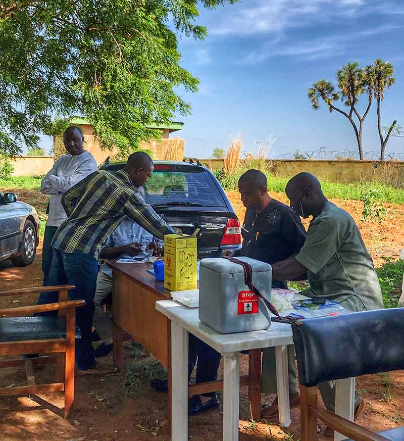 Team sitting at tables in a rural community setting