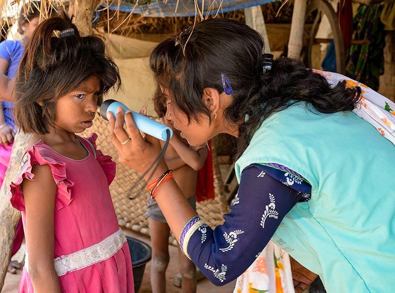 Une agente de santé oculaire examine l'œil d'une fillette avec une lampe torche.