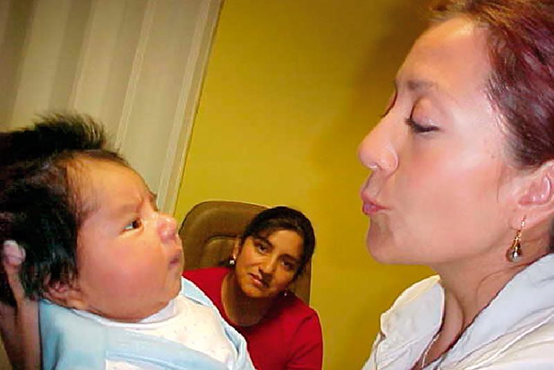 Une agente de santé oculaire tient un nourrisson qui regarde son visage, pendant que la mère de l'enfant est assise et les regarde.