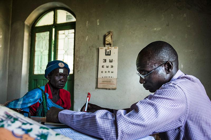 Un agent de santé est assis à son bureau et prend des notes. Une patiente est assise sur une chaise non loin du bureau, et il y a une échelle d'optotypes en E accrochée au mur.