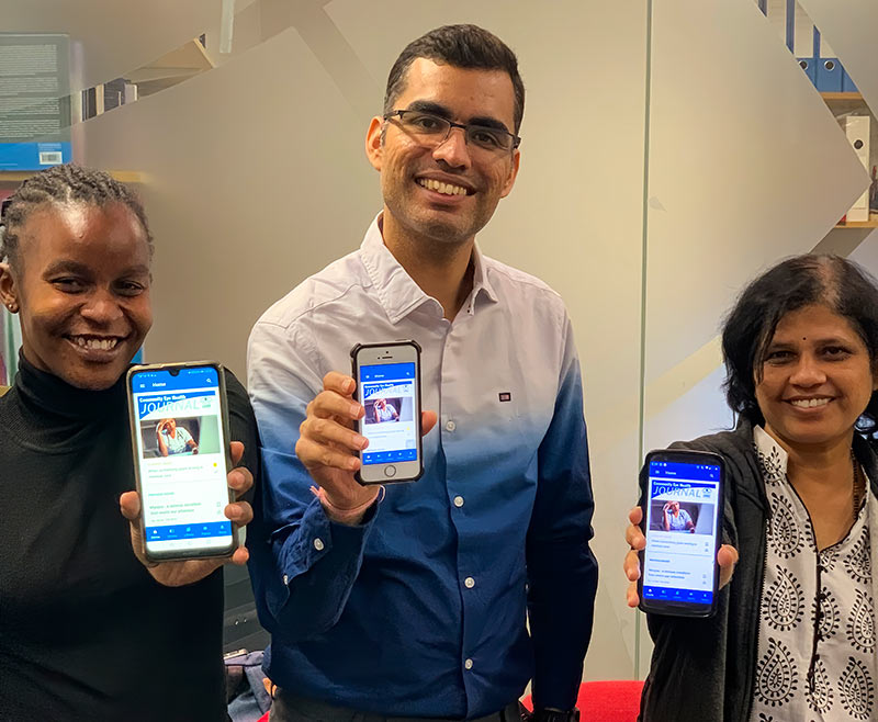 Two female and one male MSc student holding their phones towards the camera, each phone with the CEHJ App showing