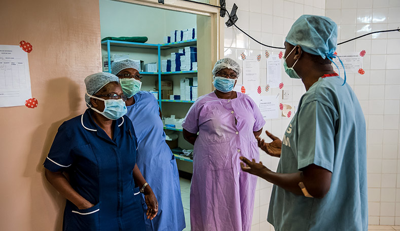 Surgeon discussing operation with 3 ophthalmic nurses outside an operating theatre