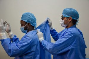 A health care worker wearing a blue gowns, blue surgical caps, surgical mask and gloves helping a colleague to fasten the back of their gown