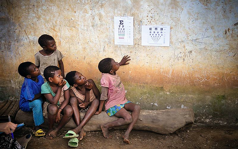 Five African children looking at a Snellen chart on the wall of a house