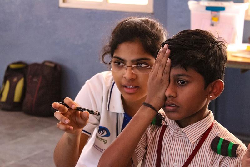 Écolier couvrant son œil droit avec la paume de sa main, pendant qu'une agente de santé oculaire se tient à côté de lui et lui fournit des explications.