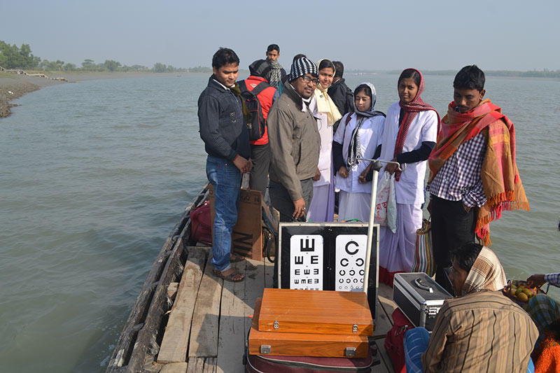 A group of people on a boat with vision charts and cases with optical refraction kits