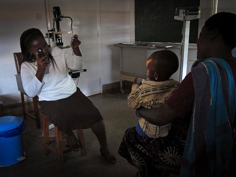 Dans une pièce sombre, un agent de santé tient un instrument pour examiner le reflet pupillaire d'un enfant, qui est assis à une certaine distance, sur les genoux d'un parent.