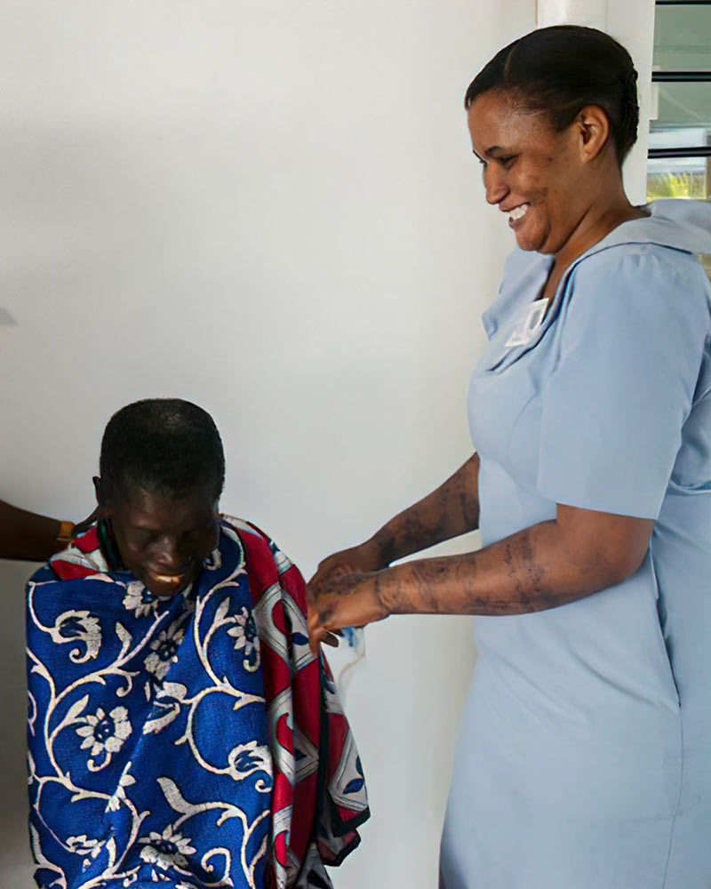 An ophthalmic nurse laughs with a patient who is also smiling