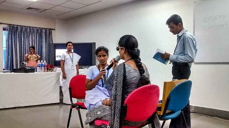 Cinq agents de santé oculaire, dont quatre femmes et un homme ; deux des femmes tiennent un microphone à la main et l'homme est en train de lire un livre.