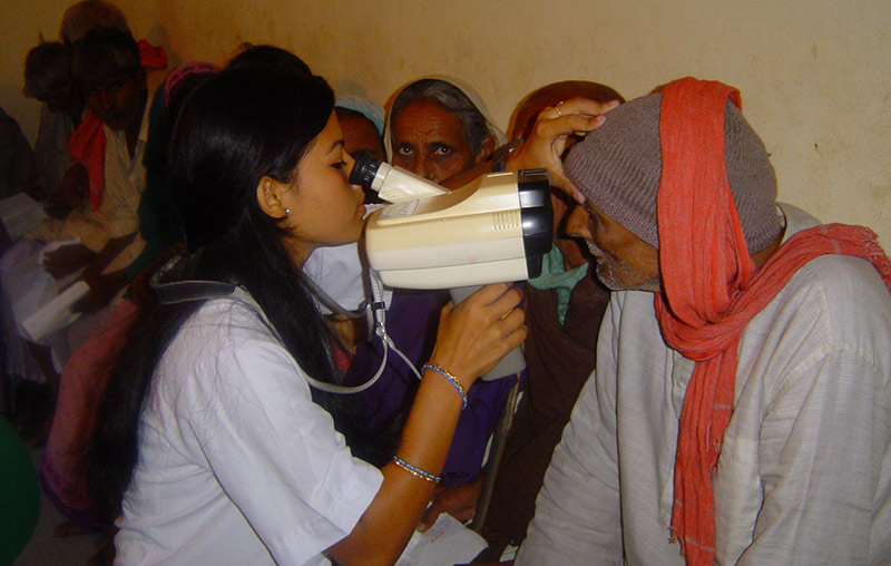 a female ophthalmic assistant holding a handheld refraction device up to the eyes of an elderly gentleman sitting down in the hallway next to other patients who are waiting