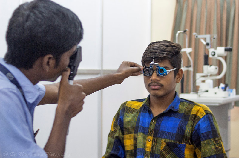 Patient wearing refracting spectacles and an optometrist holding a direct ophthalmoscope