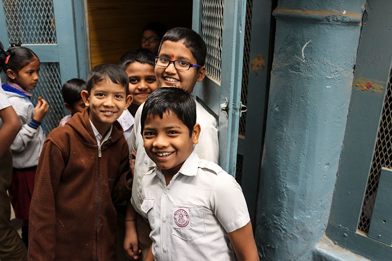 School children smiling outside a classroom