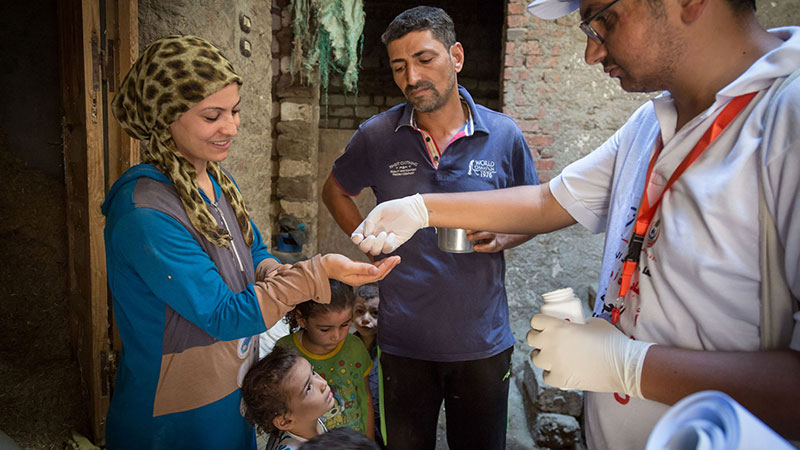 MDA to a household, man handing dose of azithromycin to a lady and her children at their front door
