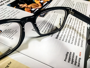 a pair of spectacles resting on top of a copy of the journal
